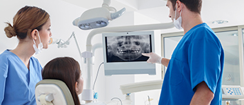 Dental staff viewing x-ray with patient